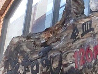 カラスによって上部が破損した寿司屋の看板。