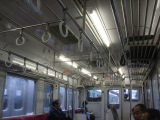 特急に比して照明間引きで薄暗い普通電車車内。
